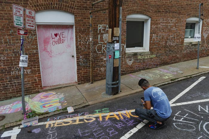 A man writes a message on the ground of the alleyway where a memorial for Heather Heyer, who was killed during 2017's Unite the Right rally, is located in Charlottesville.