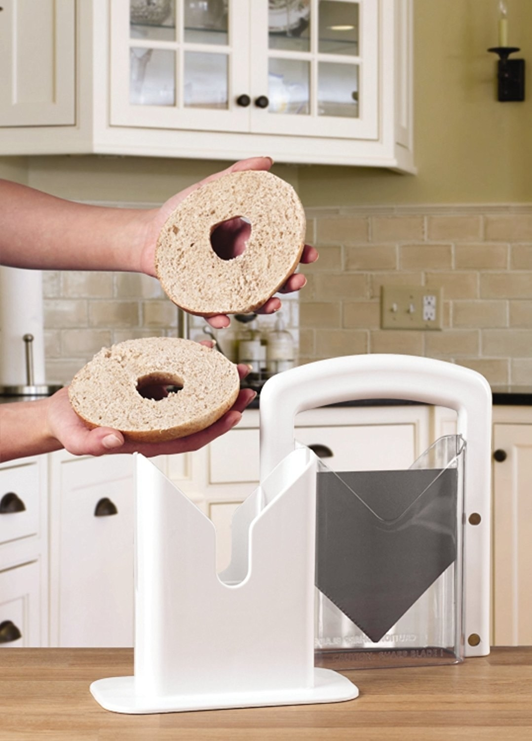 person holding clean-cut bagel after using bagel slicer to evenly slice it