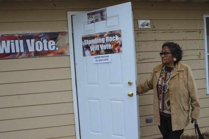 """Phyllis Young leaves the """"yellow house,"""" which is being used as the Standing Rock Sioux Tribe's get-out-the-vote headquarters."""