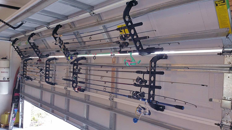 inside of garage door half open with racks on the inside of the garage doors with the fishing poles organized horizontal