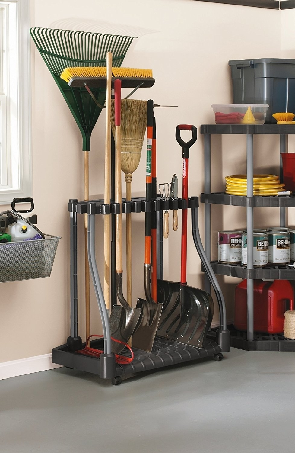 rack with rakes and heavy shovels slotted into it in a garage