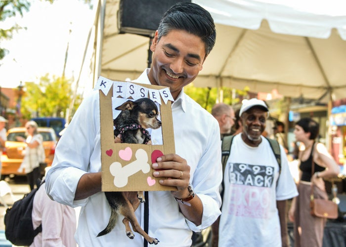 Aftab Pureval, an Ohio Democrat running for a seat in the House of Representatives, poses with a Chihuahua at the Habanero Latin American Fare, where he helped judge a pet contest in Cincinnati.