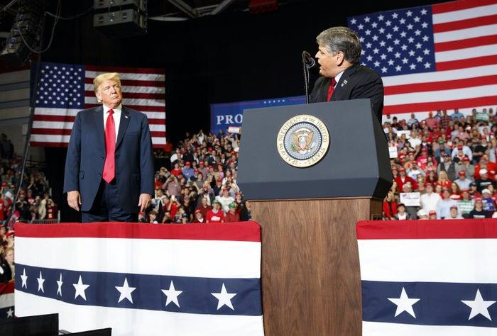 President Donald Trump listens Fox News' Sean Hannity speak during a rally in Cape Girardeau, Missouri, Monday night.