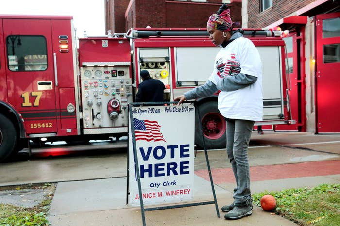 """Campaign worker Kamisthial Jones adjusts a """"Vote Here"""" sign outside a voting place."""