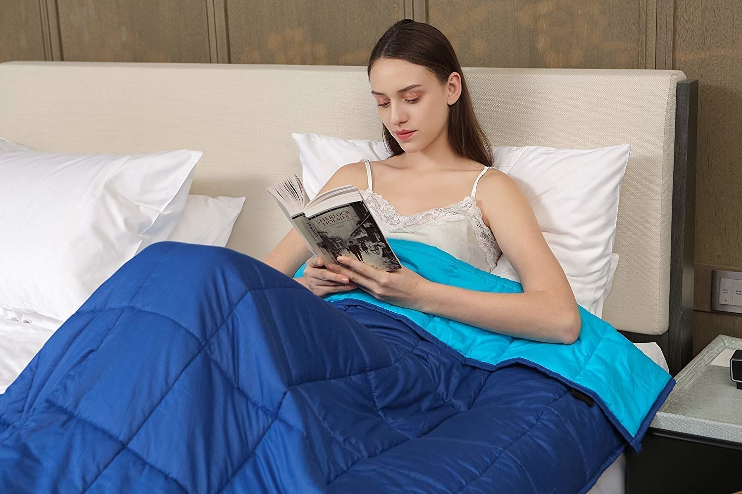A person reading a book under the weighted blanket