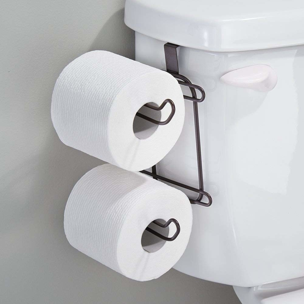 toilet with a holder for two spare rolls on toilet paper on the side of the toilet tank