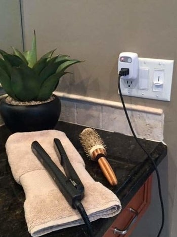 a hair straightener resting on a towel on a bathroom counter plugged up to the timer