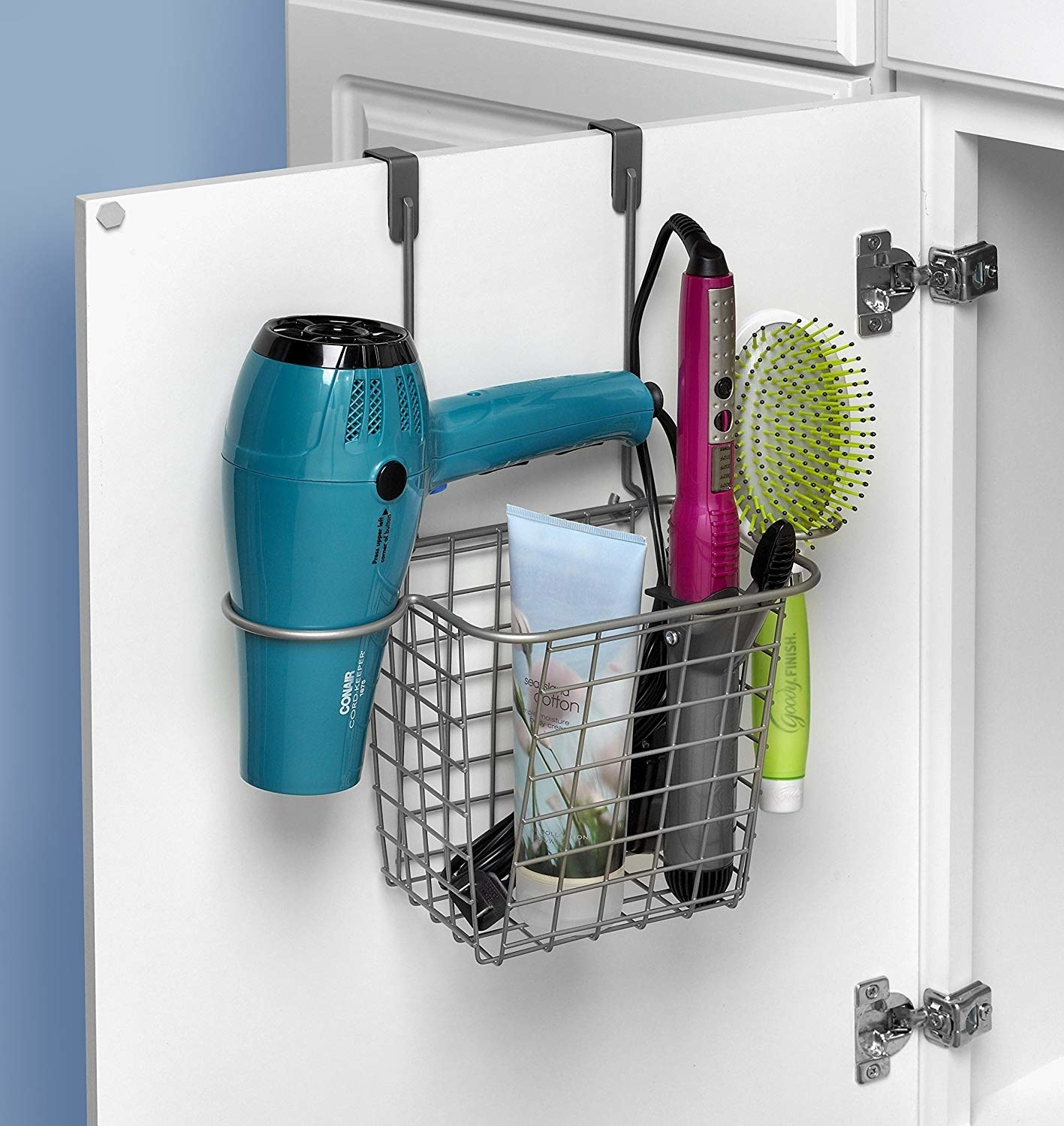 open bathroom cabinet door with basket-like over-the-door hanging organizer filled with hair tools