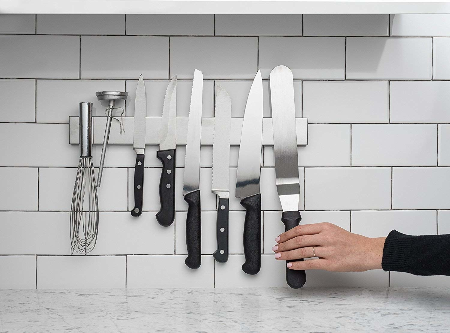 A hand placing a knife against the magnetic knife strip mounted on a tile wall