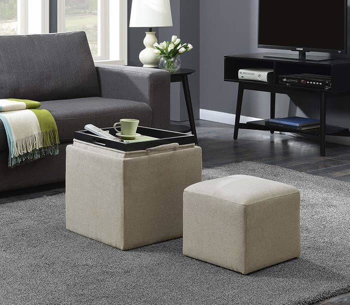 the storage ottoman with a tray on top and smaller ottoman next to it
