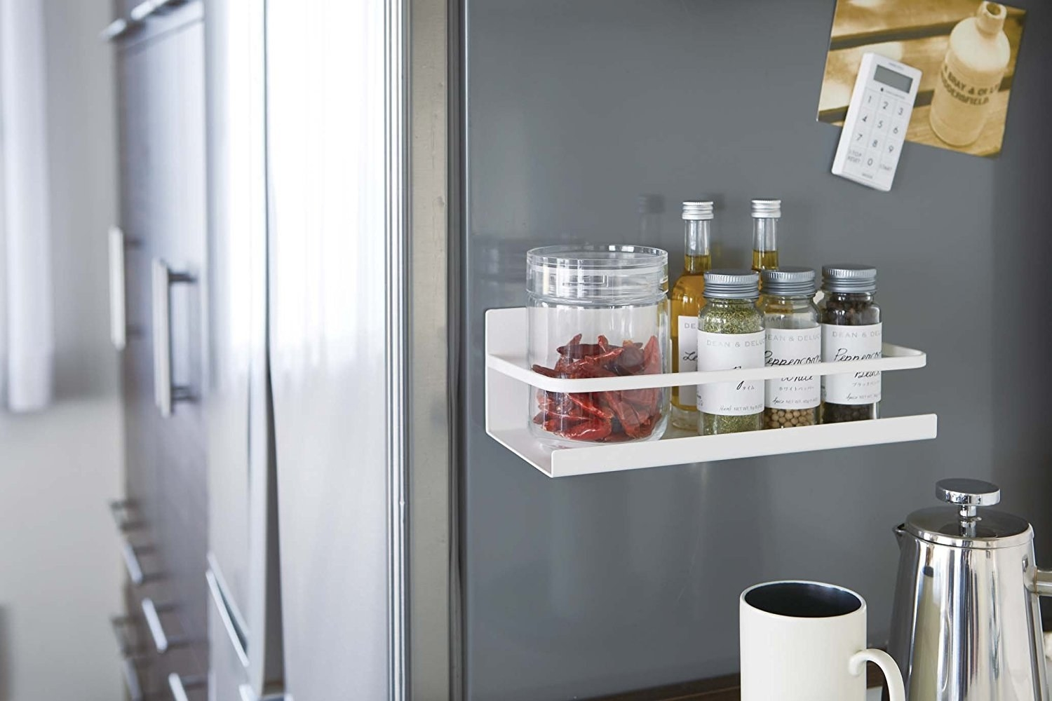 A white magnetic shelf rack holding a mix of spices and oils on the side of a refrigerator