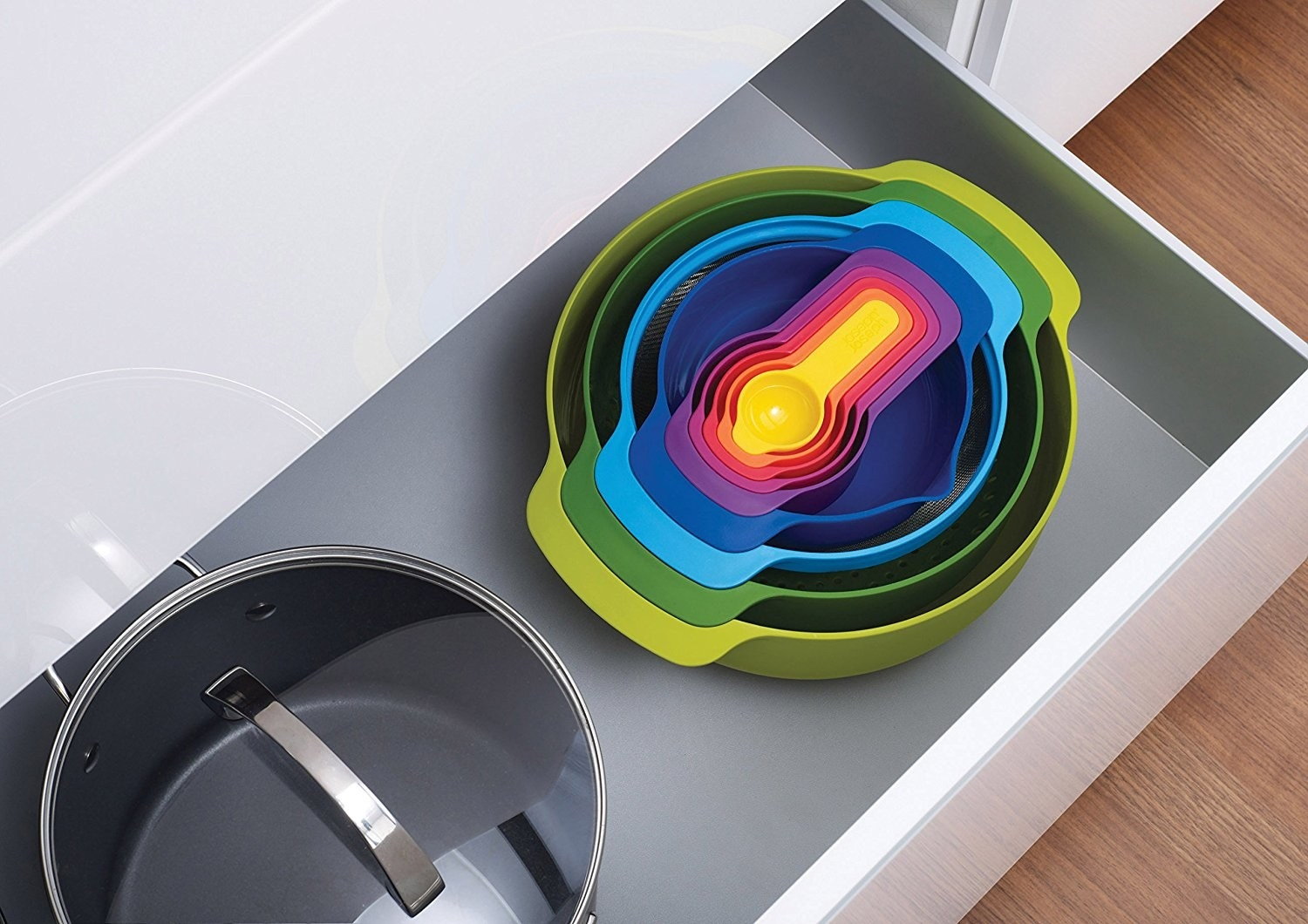 An open drawer showing the rainbow set of bowls and measuring cups nested together in one stack