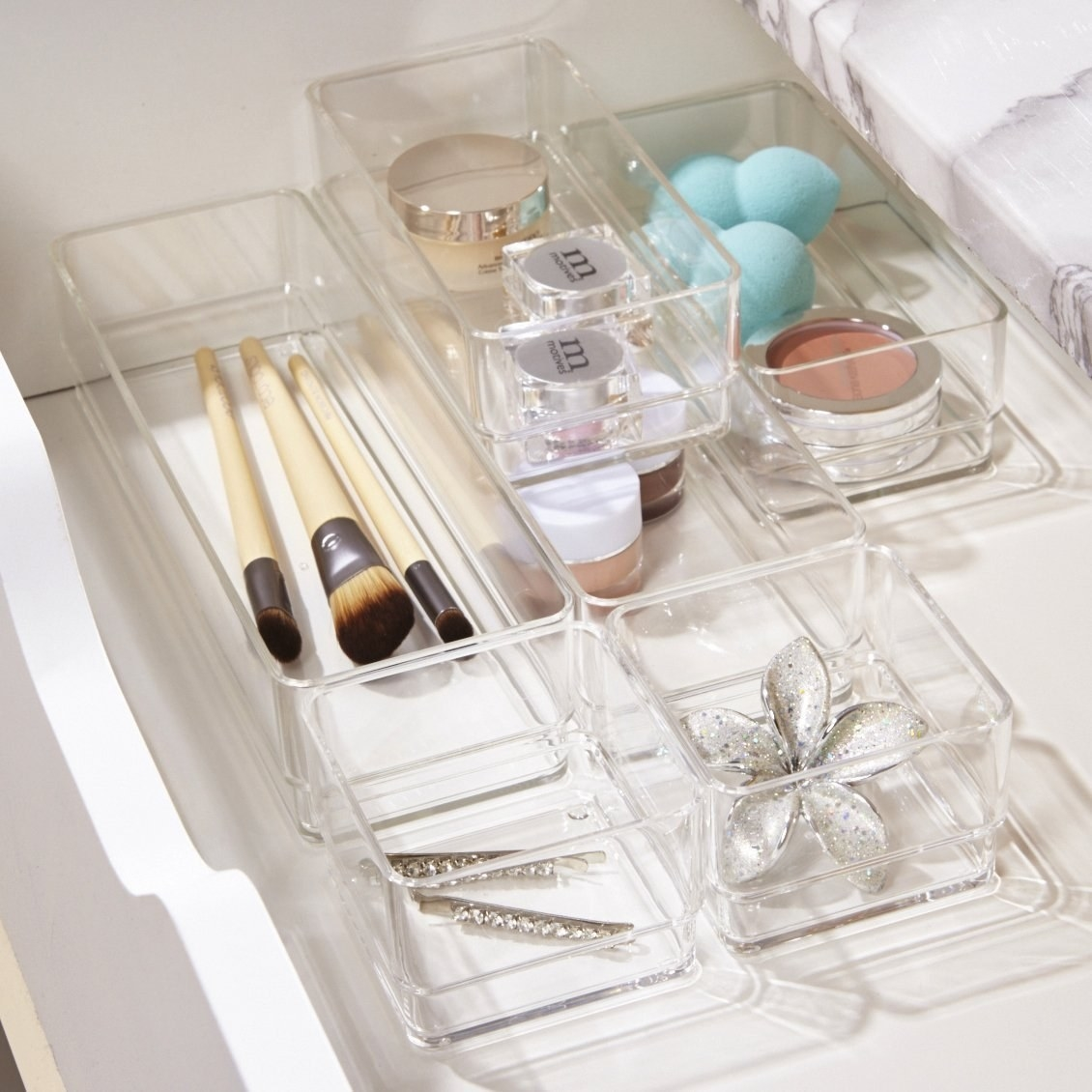 Six clear bins in a drawer organizing an array of beauty supplies