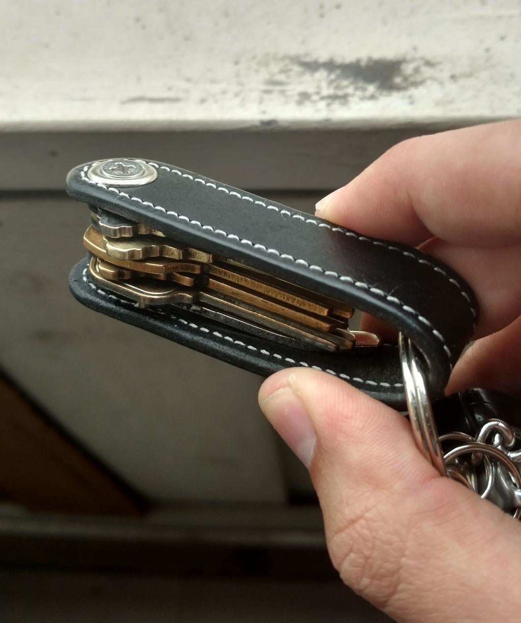 A hand holding a black leather key organizer showing multiple keys neatly stacked inside