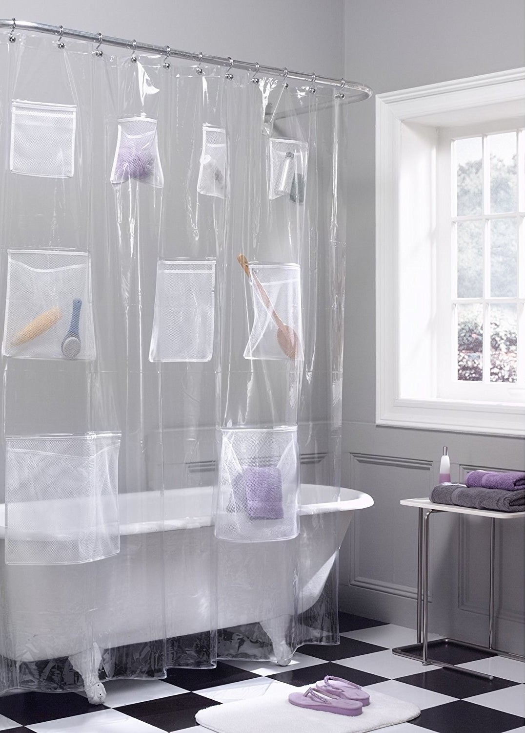A clear shower curtain around a clawfoot bathtub with pockets holding shampoo bottles, washcloths, and other bathtime accessories