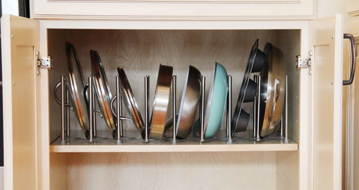 An open cabinet with pots, lids, and baking sheets neatly nested in a steel rack