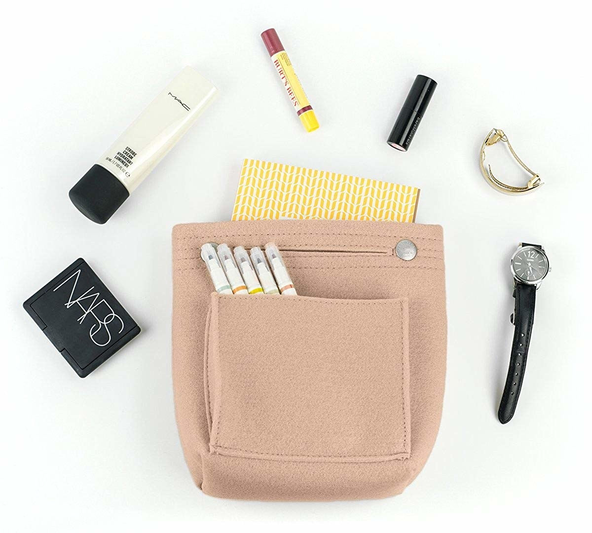 A felt purse organizer surrounded by an assortment of pens, makeup, jewelry, and a small notebook that can fit inside