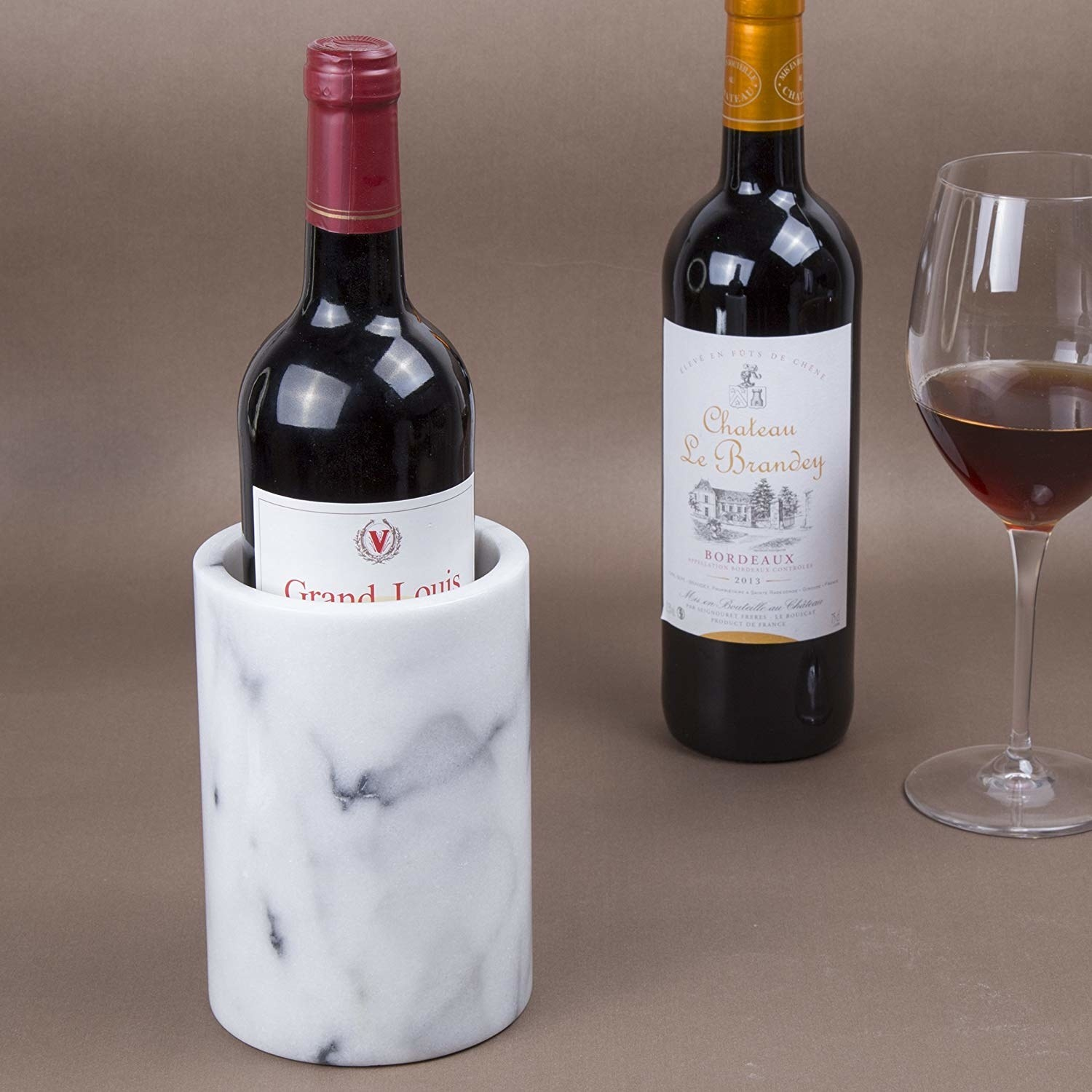 a bottle of wine in the marble crock next to another bottle and a full glass