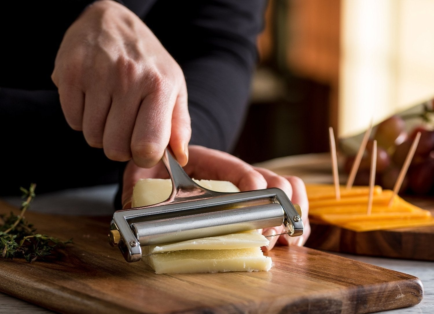 a pair of hands using the cheese slicer