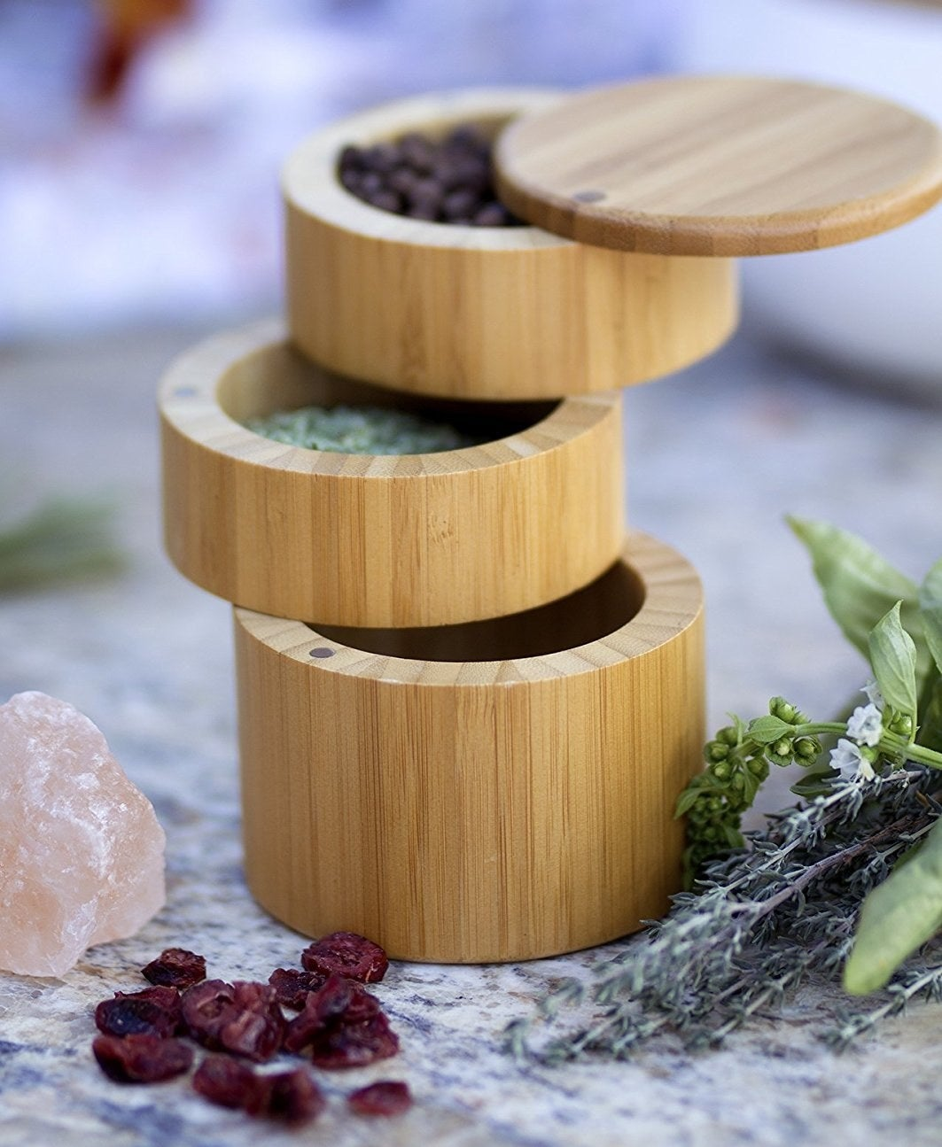 a close up of the cylindrical three tier bamboo storage box with different spices inside