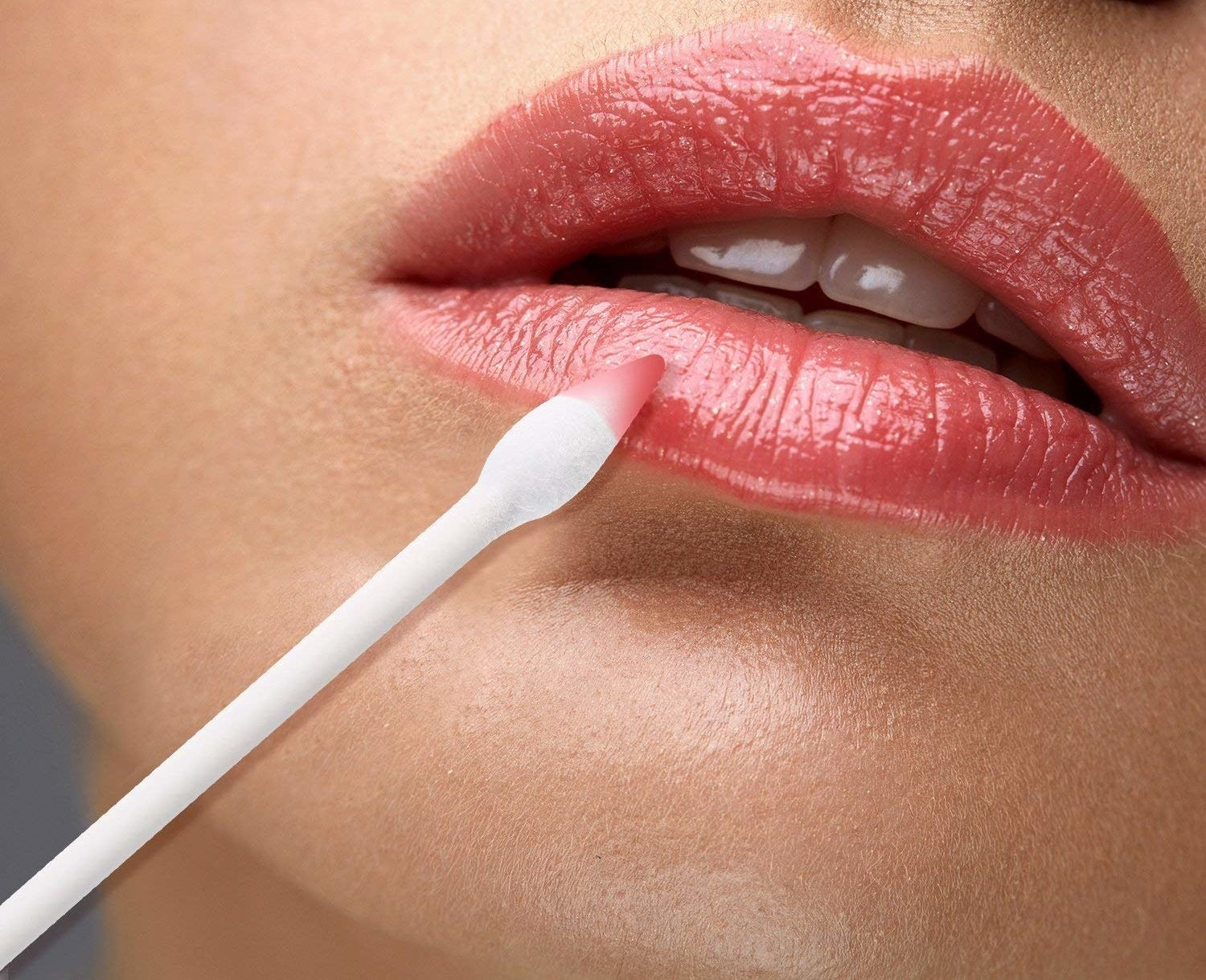 Model using the double-tipped cotton swab to fix their lipstick