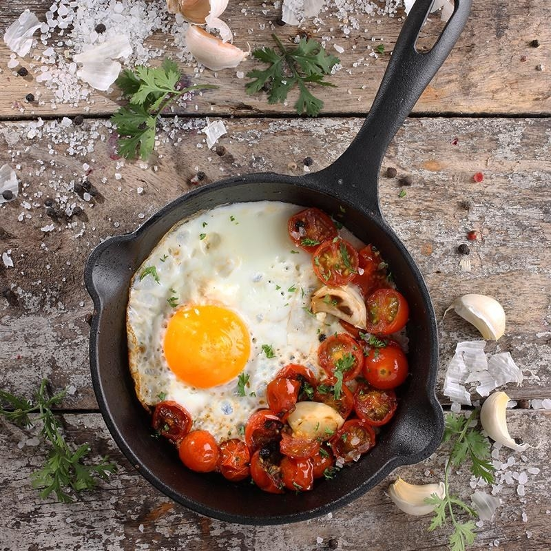 Cast iron skillet with eggs and tomatoes inside on table