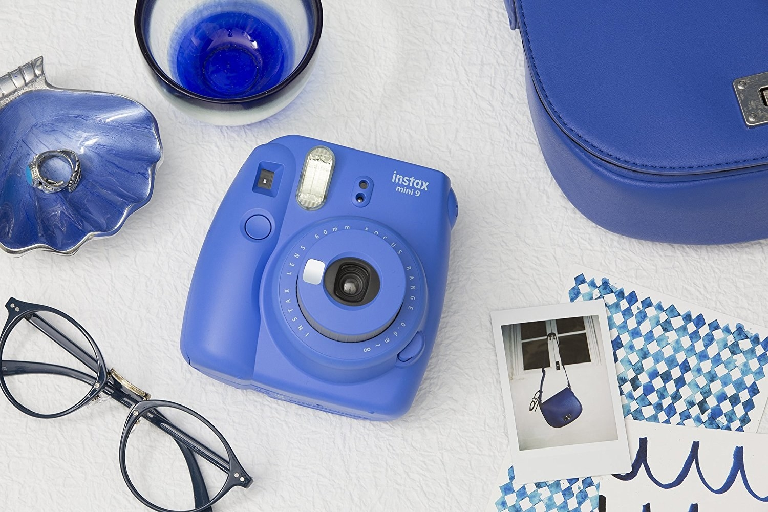 Camera on white background next to glasses and various items