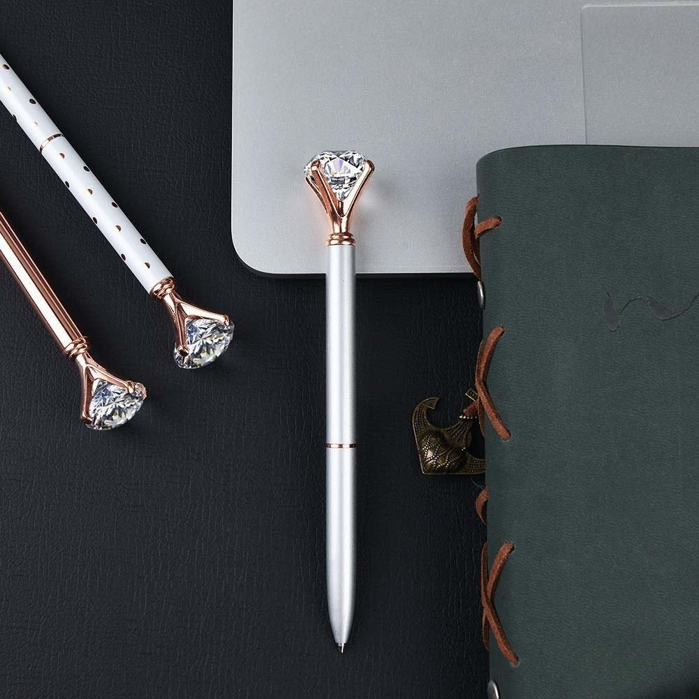 Three diamond pens next to notebook