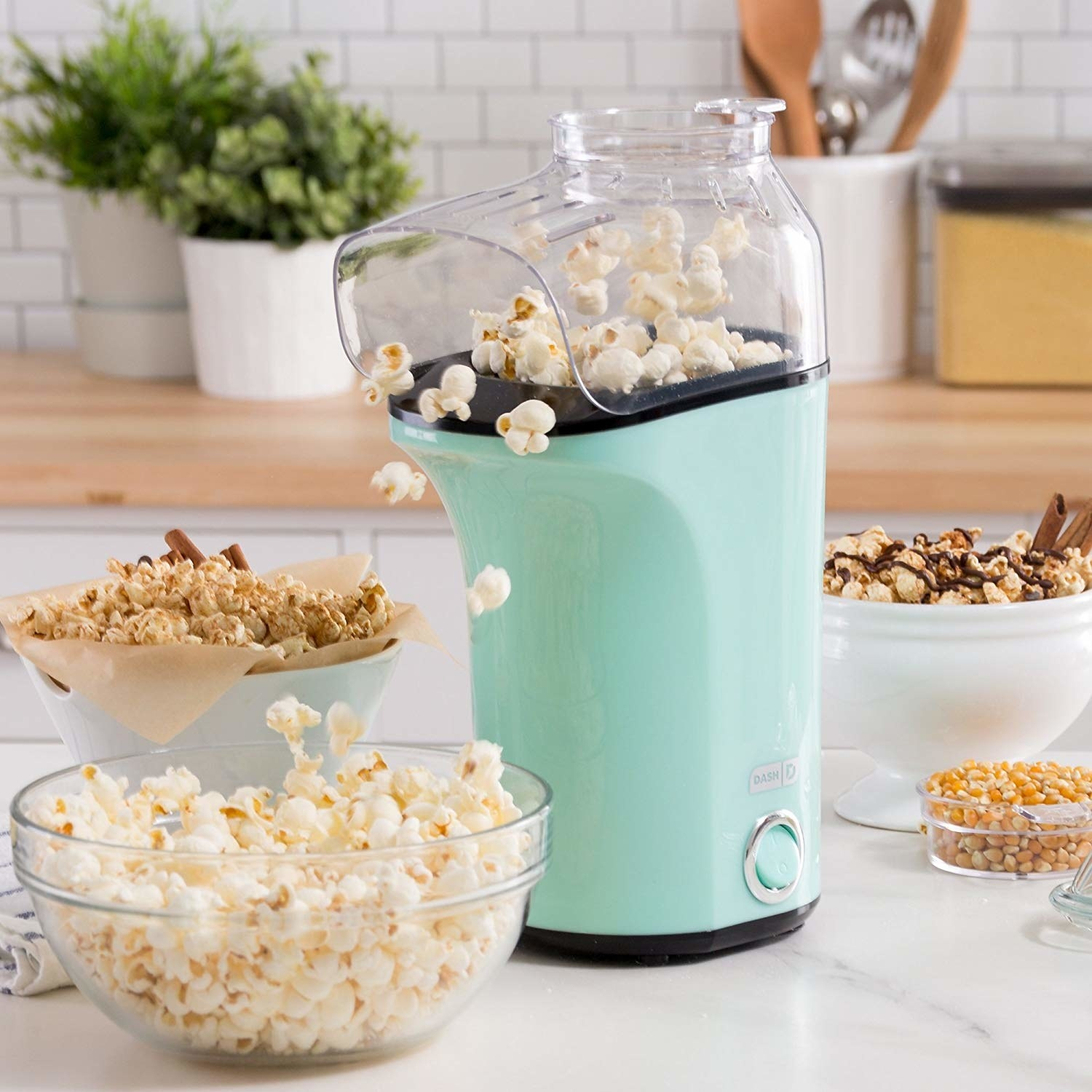 the popcorn machine dispensing popcorn into a bowl next to bowls of other various snacks
