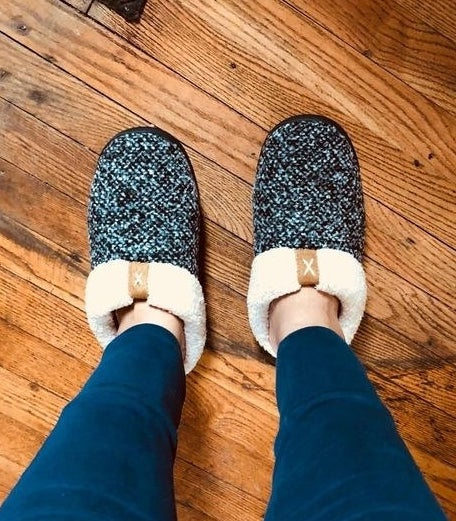 reviewer's feet in tweed and shearling slippers with open backs