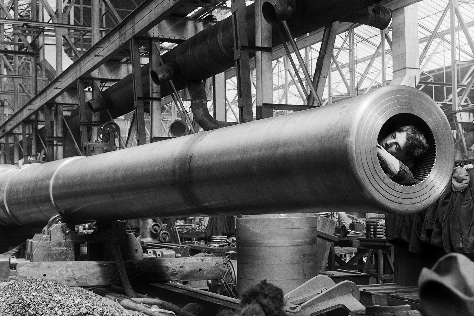 A war worker cleans inside the barrel of a naval gun at an Ordnance Works factory in London, circa 1918.