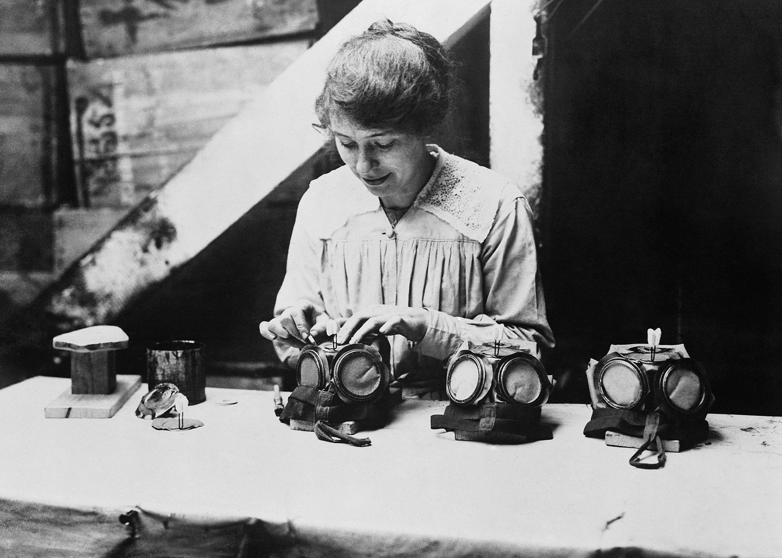 A war worker fixes nose clips onto gas masks at a factory in London, circa 1918.