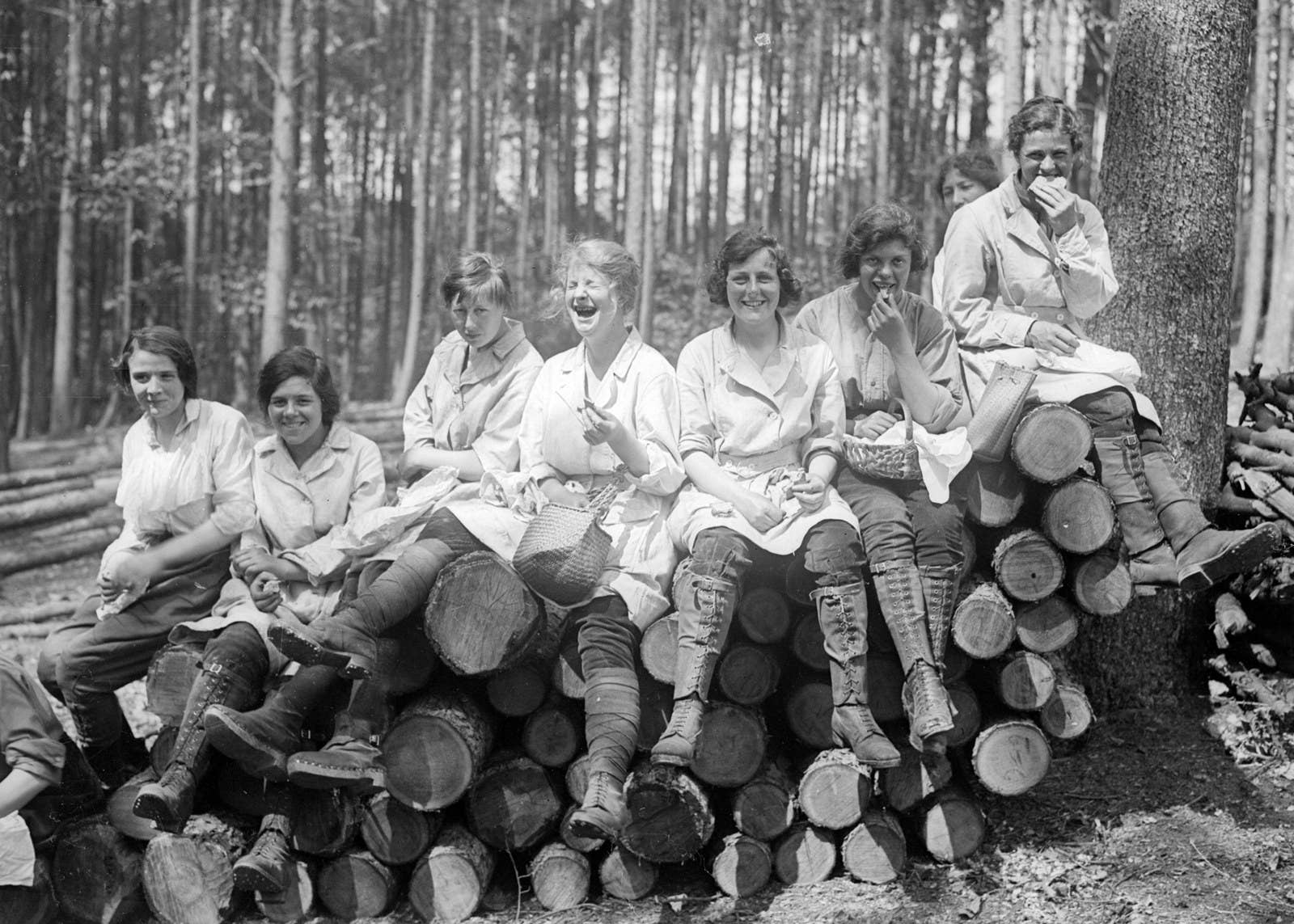 Women forestry workers sit on a pile of logs enjoying their lunches, 1918.