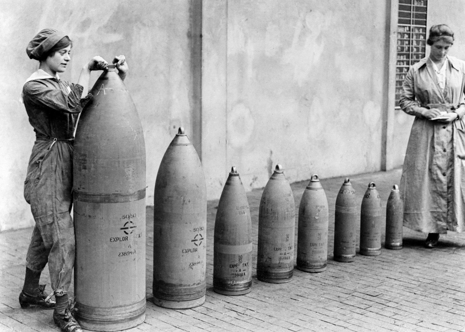 Two munitions workers stand beside examples of the shells produced at the National Shell Filling Factory in England, circa 1917.