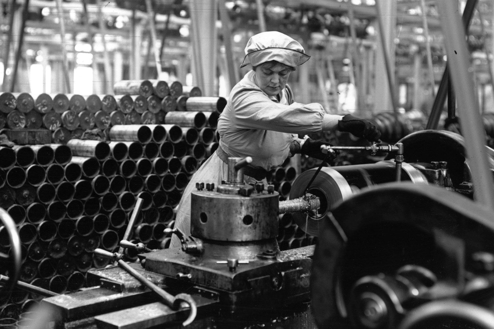 A munitions worker operating a machine in an armaments factory, circa 1915.