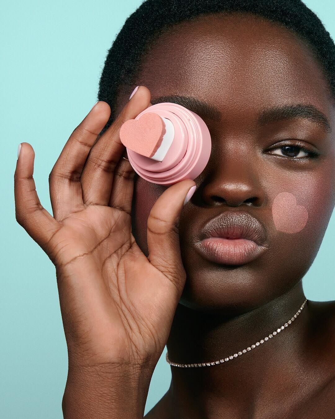 model wears a translucent pink heart on cheek and shows the stamper