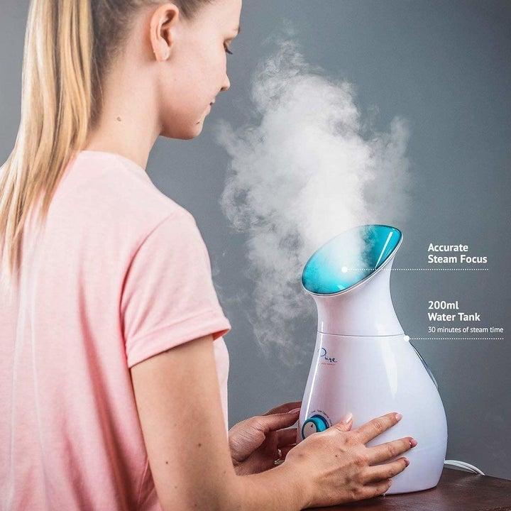 model holds steamer to face
