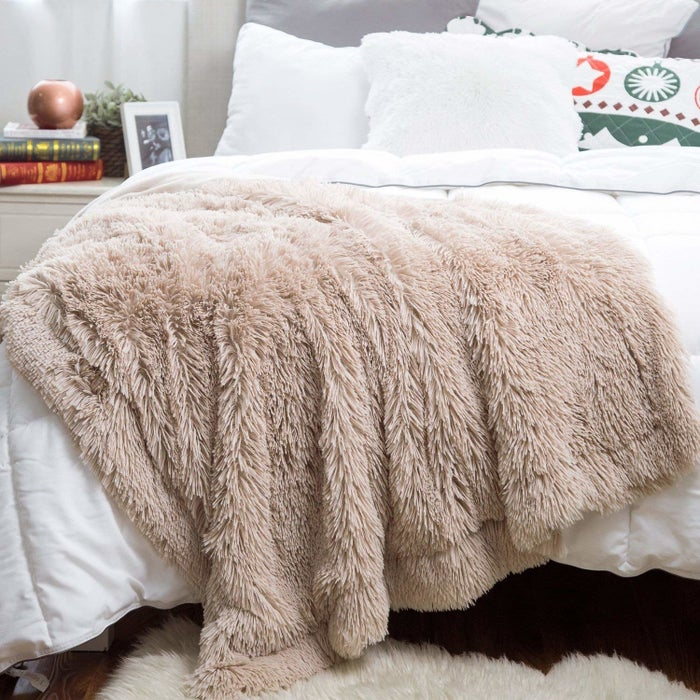 """Promising review: """"This is a great quality blanket, so amazingly soft. My cats are in love with this blanket. I'm in love with this blanket. I bought one for my couch, and the day it came, I went back and bought another for my bed. Shaggy camel is the prettiest rosy-camel color. I find this blanket does not shed, either, which is a miracle."""" —Shazia M.Get it from Amazon for $29.99 (available in two sizes and three styles)."""