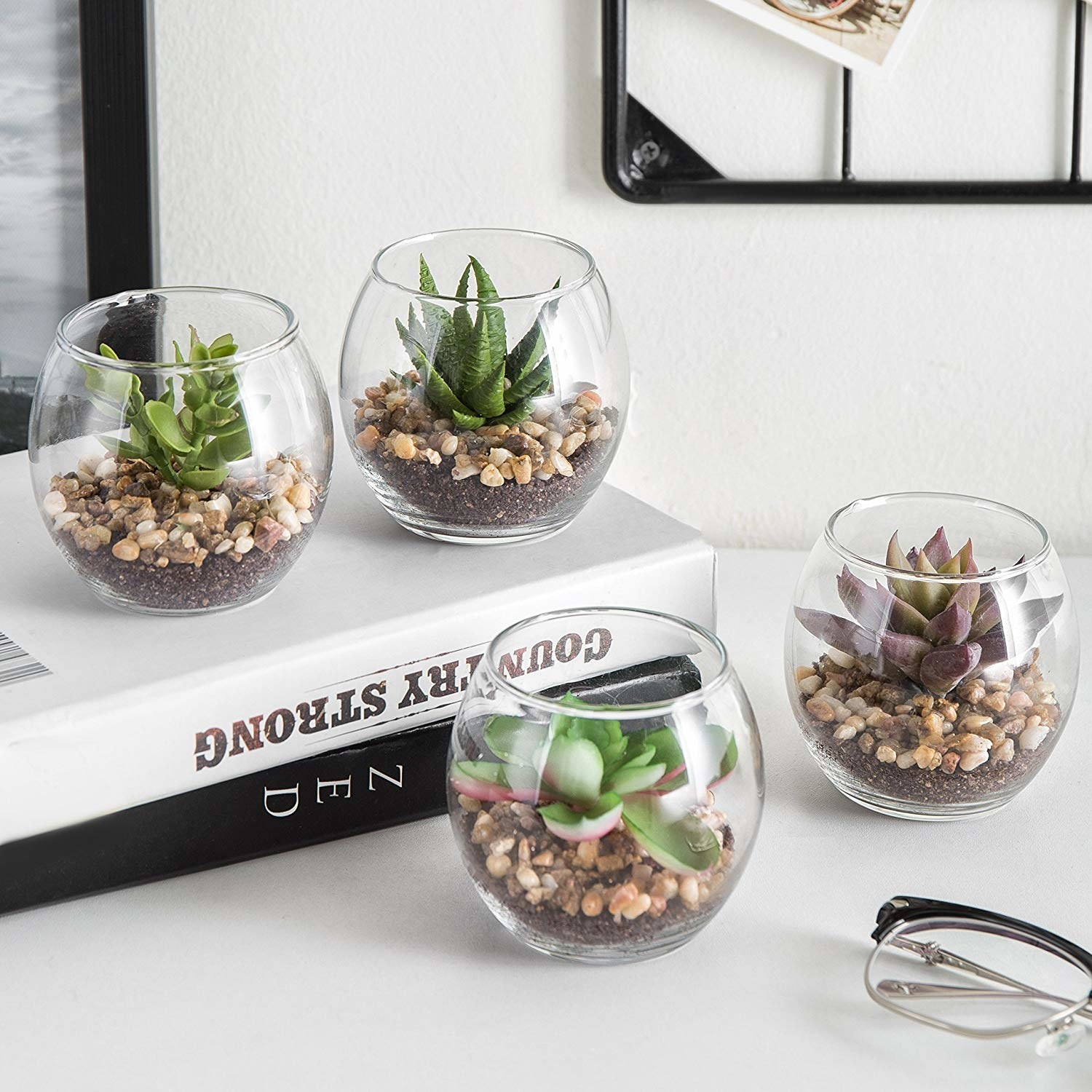 four different  fake succulents in clear sphere planters