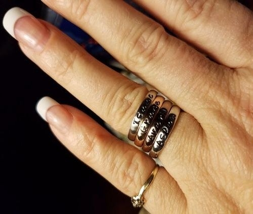 reviewer wearing four stacked engraved rings