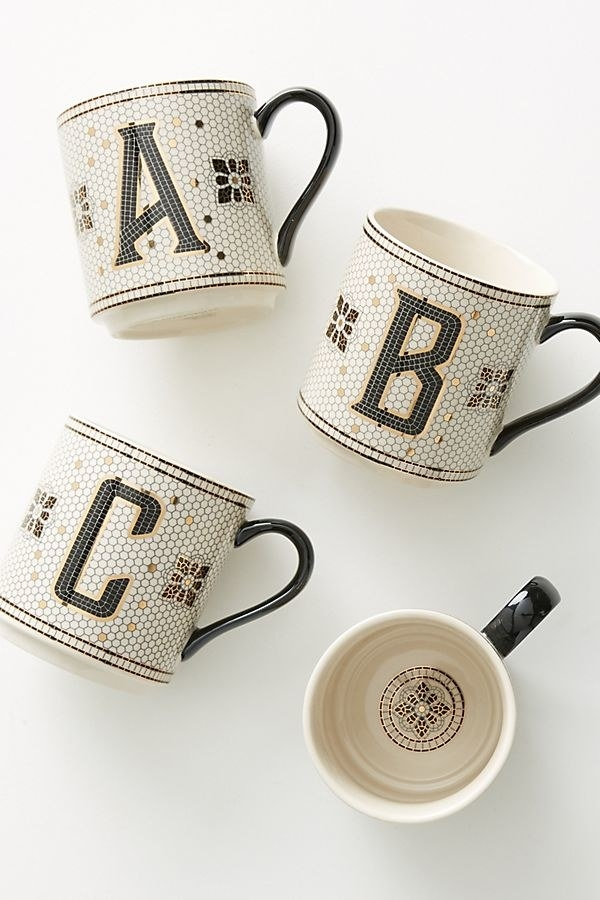 mugs monogrammed A, B, and C in a style that looks like black, white, and gold vintage tile