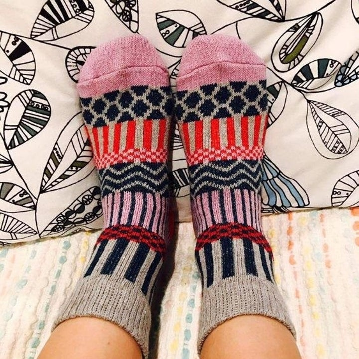 reviewer wearing a pair of socks with green, red, pink, and gray in them
