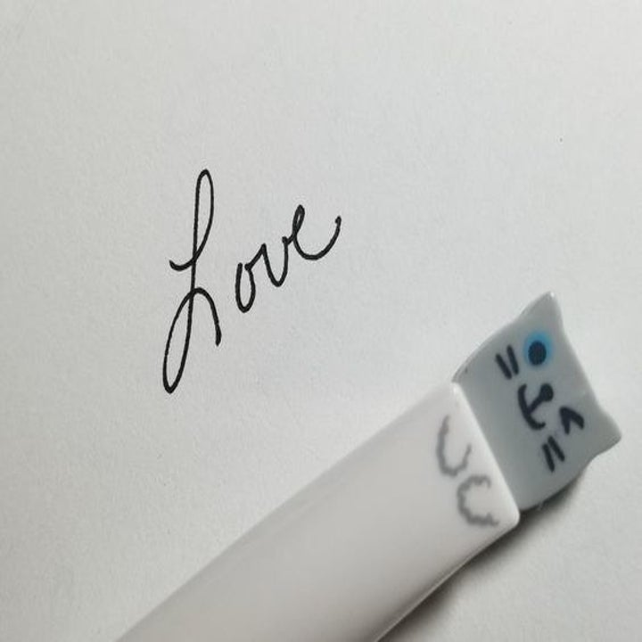 """close-up of one cat pen along with the word """"Love"""" written with ink from the pen"""