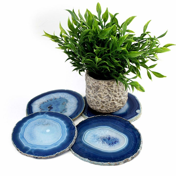 four circular blue agate coasters, one with a small plant sitting on it