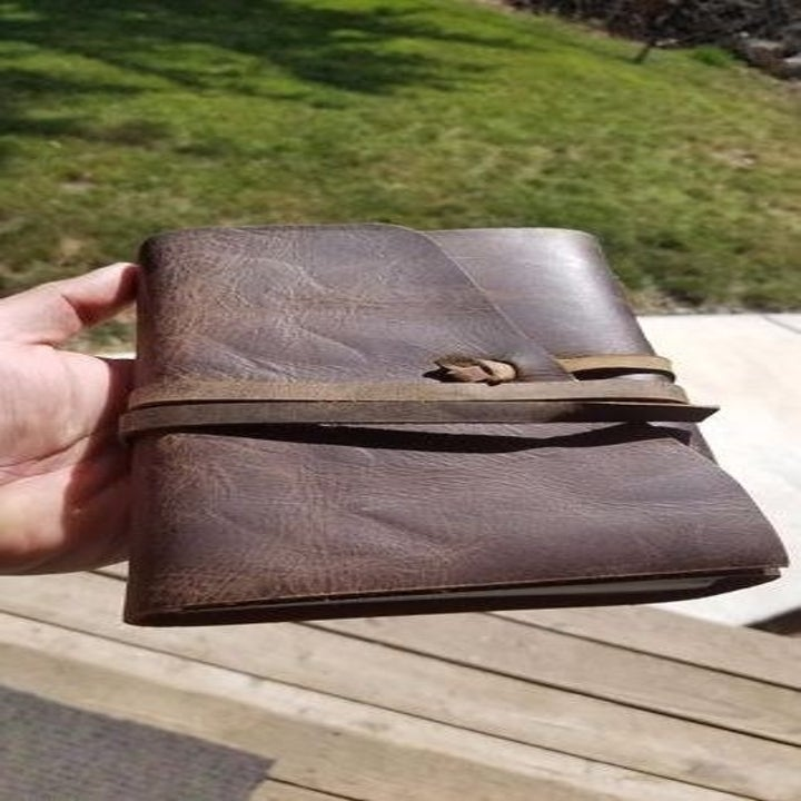 reviewer's hand holding the journal with its leather straps binding it closed