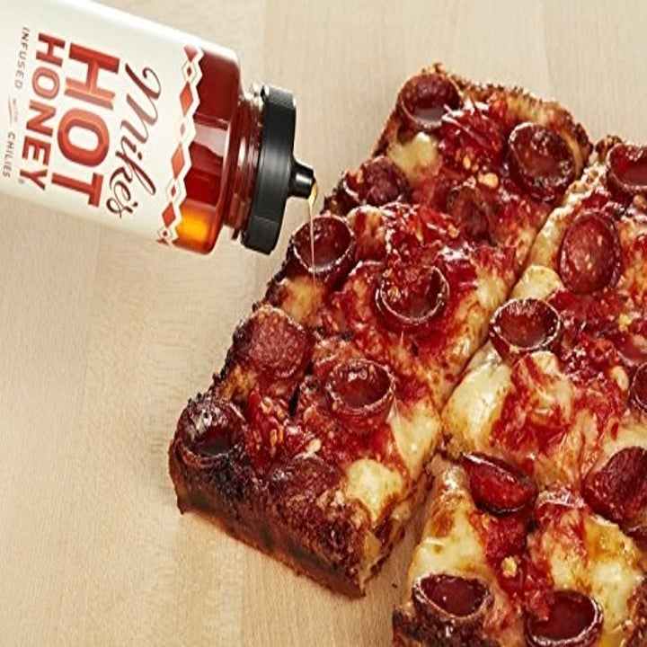 the honey being poured on pepperoni pizza and are you salivating because I sure am