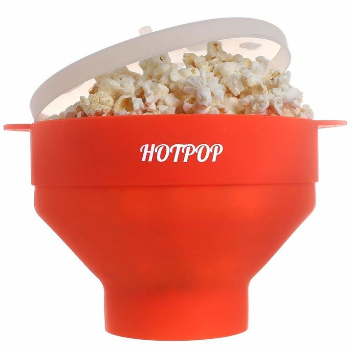 a red bowl of popcorn with the lid partially pulled open and popcorn in it