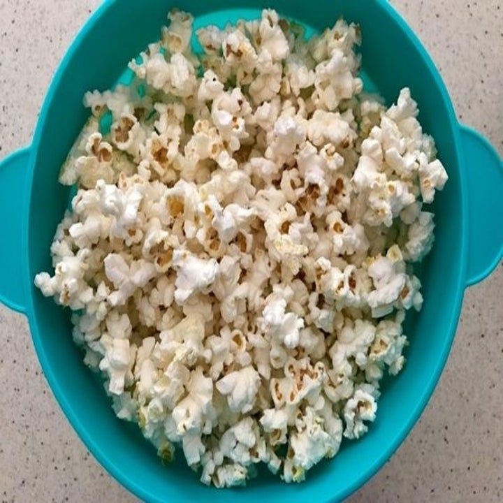 reviewer's bowl in blue with popcorn in it and no lid