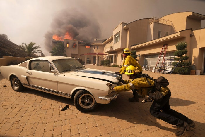 Firefighters push a vehicle from a garage as a home burns in Malibu on Nov. 9.