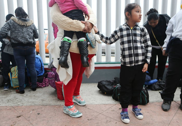 A migrant woman waited Friday with her two daughters to ask for asylum in the US.